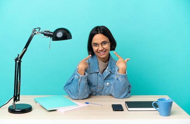 Kobieta młodych studentów rasy mieszanej studiuje na stole, dając kciuki do góry gestu
