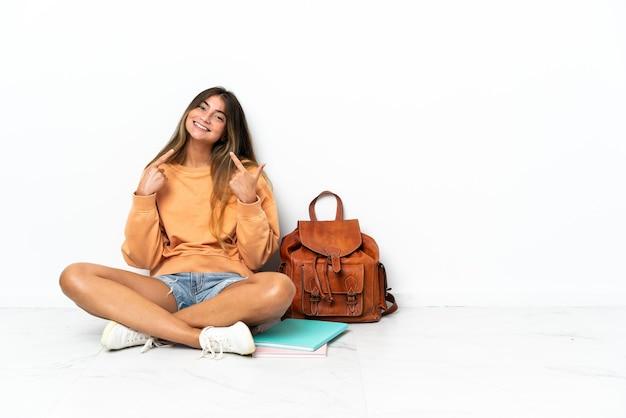 Kobieta młodych studentów siedzi na podłodze z laptopem na białym tle, dając kciuk w górę gestu