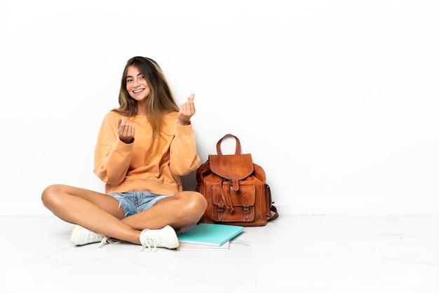 Kobieta młodych studentów siedzi na podłodze z laptopem na białym tle dokonywania gestu pieniędzy