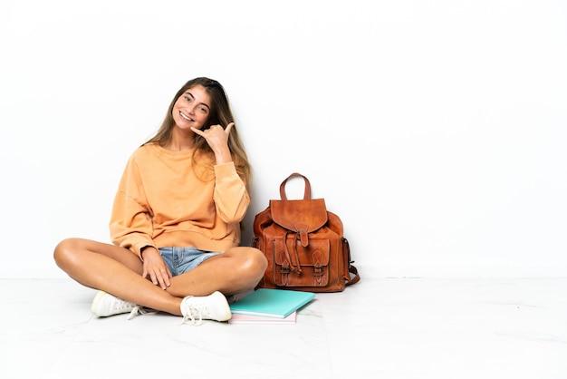 Kobieta młodych studentów siedzi na podłodze z laptopem na białym tle dokonywanie gestu telefonu. oddzwoń do mnie znak