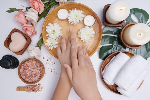 Kobieta moczy ręce w misce z wodą i kwiatami, zabieg i produkt dla kobiecych stóp i dłoni, kamyczki do masażu, woda perfumowana z kwiatami i świecami, relaks. leżał na płasko. widok z góry.