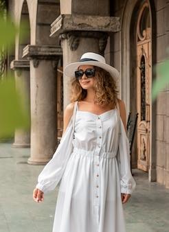 Kobieta moda dziewczyna patrząc na stare miasto. dziewczyna w europie. koncepcja podróży. piękna dziewczyna w białej sukni i kapeluszu. modelka na tle ulicy. styl życia, podróże, wakacje, turystyka