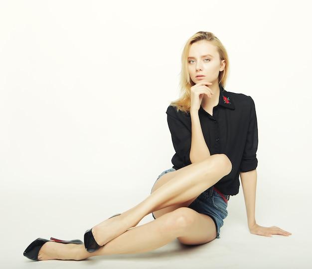 Kobieta moda model stwarzających w studio na białym tle