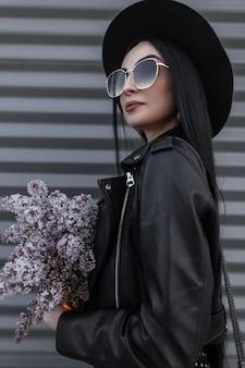 Kobieta moda portret z pięknym bukietem fioletowych kwiatów w modnym kapeluszu w okularach przeciwsłonecznych w stylowej skórzanej kurtce w pobliżu zabytkowej metalowej ściany w mieście. urocza dziewczyna w młodzieżowym stroju z liliowymi roślinami
