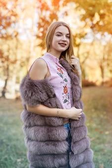 Kobieta moda. uśmiechnięta dziewczyna w futrze posin w jesiennym parku z drzewami i bluszczem