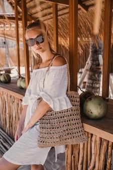 Kobieta moda w bieli za drewnianą kawiarnią