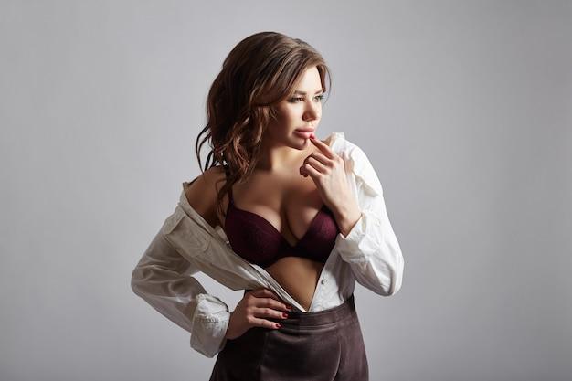 Kobieta moda w bieliźnie i białej koszuli z otwartą klatką piersiową i krótką spódniczką. sexy dziewczyna pozuje na ciemnym tle. pewna siebie kobieta o pięknym ciele, dużych oczach i pełnych ustach.