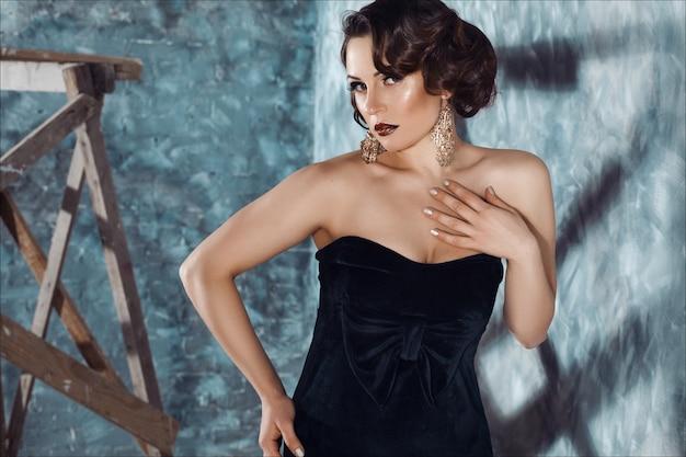 Kobieta moda w czarnej sukni z pięknem makijaż i fryzurę retro.