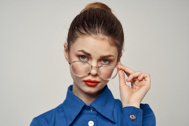 Kobieta moda w jasnej niebieskiej koszuli patrząc na okulary