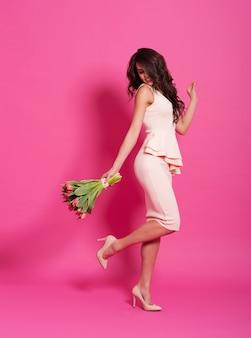Kobieta moda z bukietem różowych tulipanów