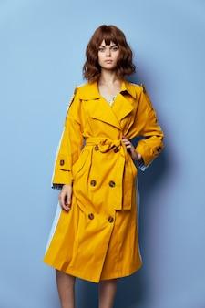 Kobieta moda żółty płaszcz ręka na pasku z niecierpliwością na jasny makijaż