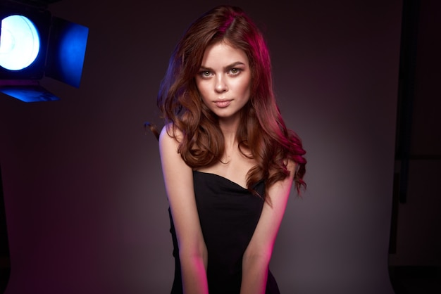 Kobieta model czarna sukienka pozowanie studio mody fryzurę ciemnym tle. zdjęcie wysokiej jakości