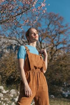 Kobieta model pozuje pod kwitnącym drzewem