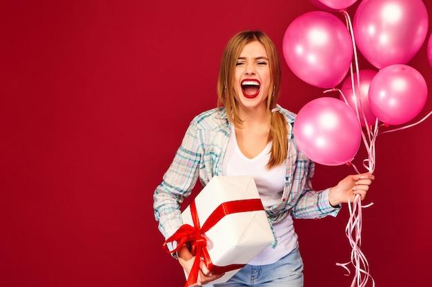 Kobieta model świętuje i trzyma pudełko z prezentem teraźniejszym i różowymi balonami