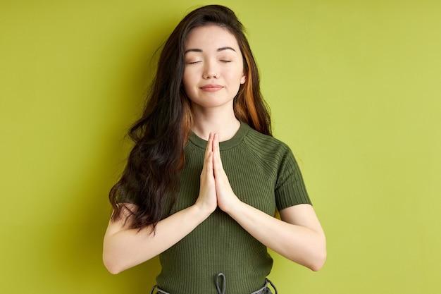 Kobieta modląc się z rękami razem prosząc o przebaczenie, uśmiechając się z zamkniętymi oczami, przyjemna brunetka kobieta na białym tle na zielonym tle