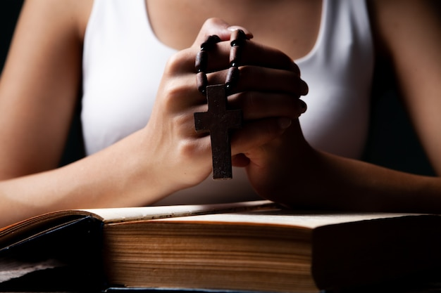 Kobieta modląca się na książce trzymającej krzyż
