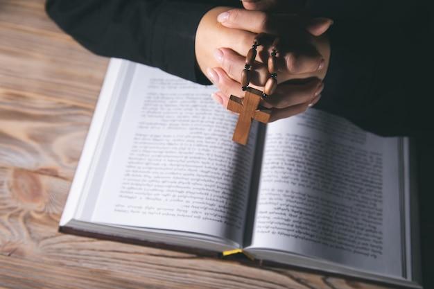 Kobieta modląca się trzymająca krzyż na piśmie świętym