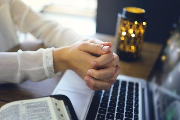 Kobieta modli się przez wiarę z laptopem komputerowym, koncepcja usług kościelnych online, koncepcja kościoła online w domu, duchowość i religia.