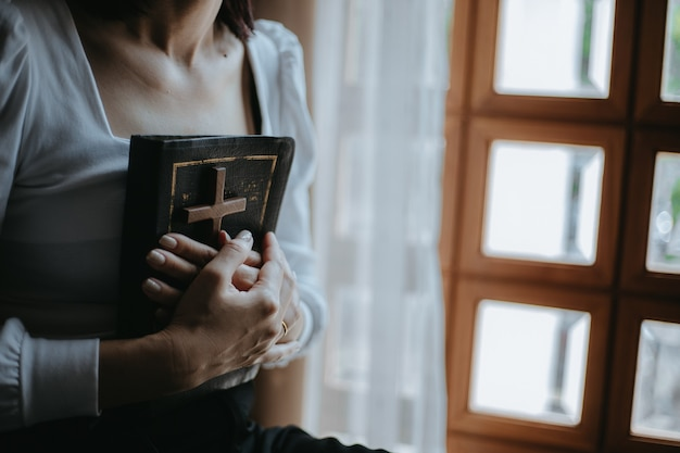 Kobieta modli się z biblią i drewnianym krzyżem w kościele