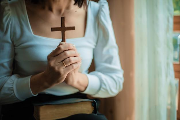 Kobieta modli się z biblią i drewnianym krzyżem.