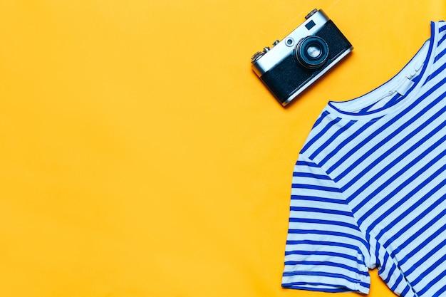 Kobieta mody podróży flatlay tym retro aparat fotograficzny, t-shirt. widok z góry, płaski układ