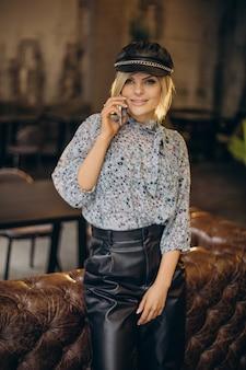 Kobieta mody w kawiarni rozmawia przez telefon