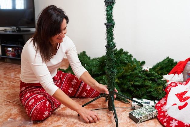 Kobieta montująca choinkę w swoim salonie