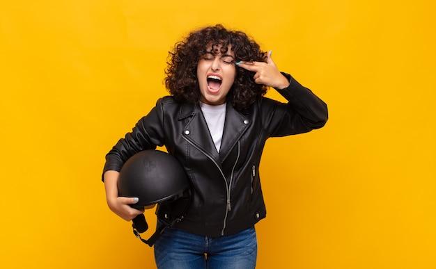 Kobieta motocyklista szuka nieszczęśliwego i zestresowanego, gest samobójczy robi znak pistoletu ręką, wskazując na głowę