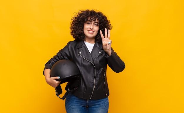 Kobieta motocyklista uśmiechnięta i wyglądająca przyjaźnie, pokazująca numer trzy lub trzeci z ręką do przodu, odliczający