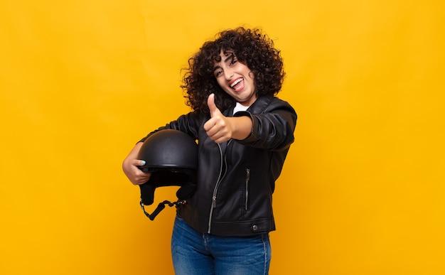 Kobieta motocyklistka czująca się dumna, beztroska, pewna siebie i szczęśliwa, uśmiechająca się pozytywnie z uniesionymi kciukami