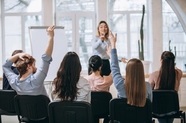 Kobieta mówca dając prezentację w hali w warsztatach uniwersyteckich. sala widowiskowa lub konferencyjna