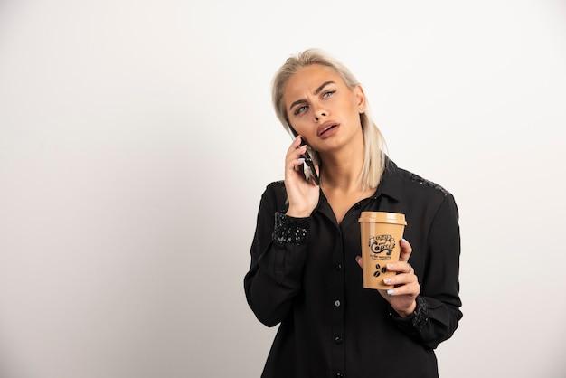 Kobieta mówi na telefon komórkowy i trzyma filiżankę kawy. wysokiej jakości zdjęcie