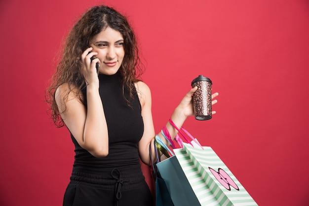 Kobieta mówi przez telefon z kubkiem i workami na czerwonym tle. wysokiej jakości zdjęcie