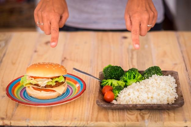 Kobieta musi wybierać między hamburgerem a warzywami i wstać, aby mieć zdrowy, wspaniały styl życia i być z siebie szczęśliwą - mężczyzna wybierz preferowany rodzaj jedzenia
