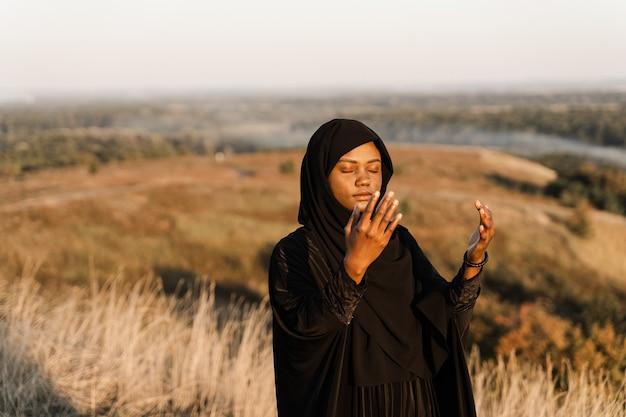 Kobieta musim modli się do allaha. afrykańska kobieta w czarnej szacie modlić się solat.