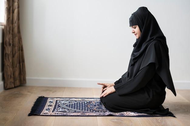 Kobieta muzułmańska modląc się w postawie tashahhud