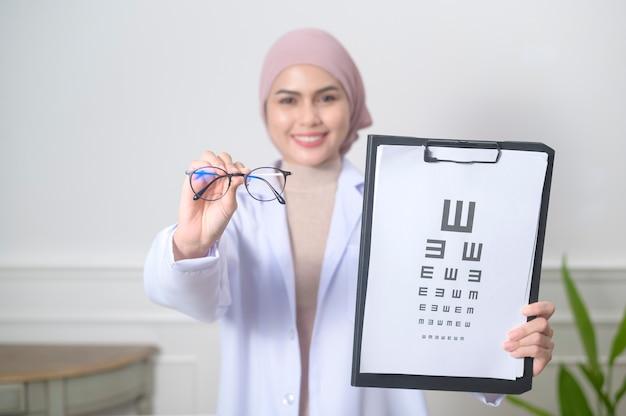 Kobieta muzułmańska okulista trzymająca test karty wzroku do pomiaru ostrości wzroku