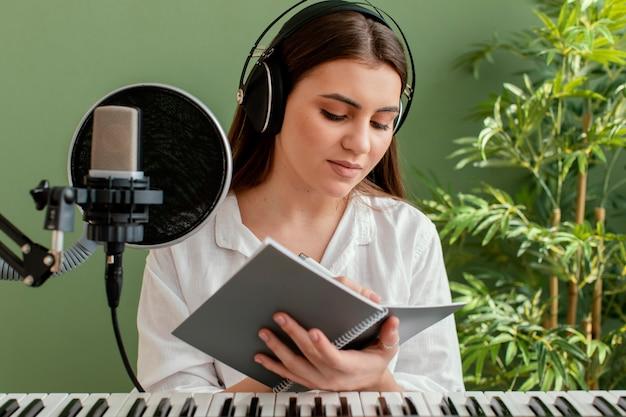 Kobieta muzyk gra na klawiaturze fortepianu i pisze piosenki podczas nagrywania