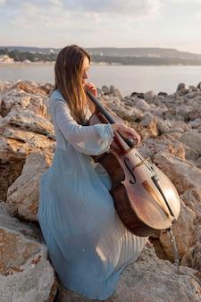Kobieta muzyk gra na wiolonczeli o zachodzie słońca na skałach