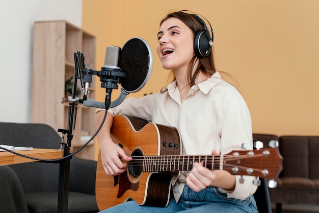 Kobieta muzyk nagrywa piosenkę i gra na gitarze akustycznej w domu