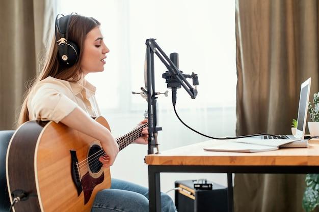 Kobieta muzyk nagrywa piosenkę w domu grając na gitarze akustycznej