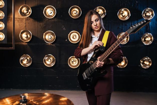 Kobieta muzyk w garniturze gra na gitarze elektrycznej