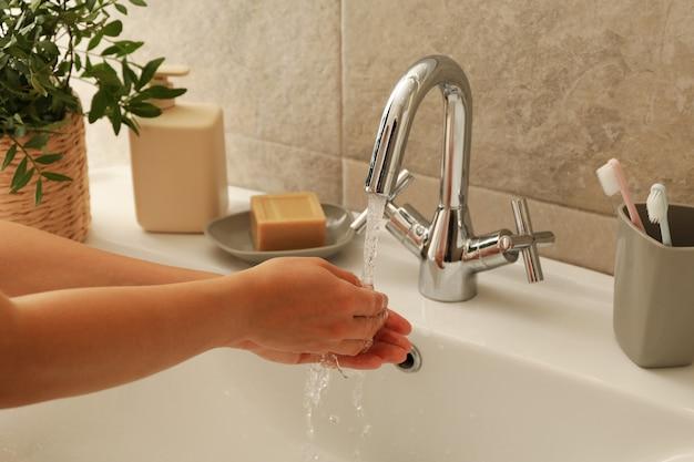 Kobieta mycia rąk pod kranem w zlewie
