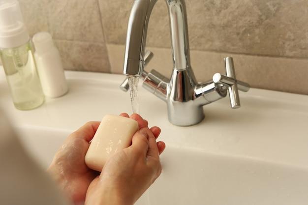 Kobieta mycia rąk w umywalce w łazience mydłem