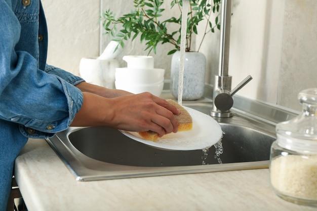 Kobieta mycia talerza w zlewie kuchennym