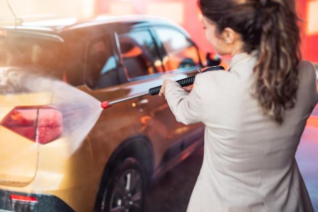 Kobieta mycie samochodu na myjni samochodowej za pomocą wody pod wysokim ciśnieniem.