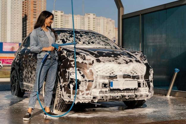 Kobieta mycie samochodu na zewnątrz