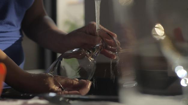 Kobieta myjąca kieliszek w kuchni