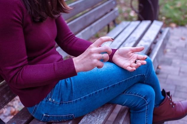 Kobieta myjąca ręce alkoholowym żelem dezynfekującym siedząca na ławce