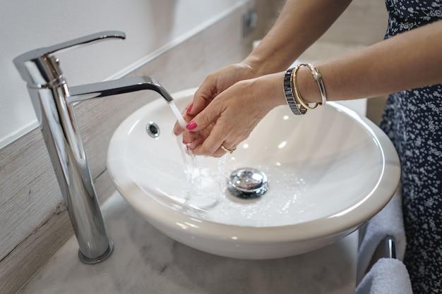 Kobieta myjąca ręce w białej okrągłej umywalce w łazience